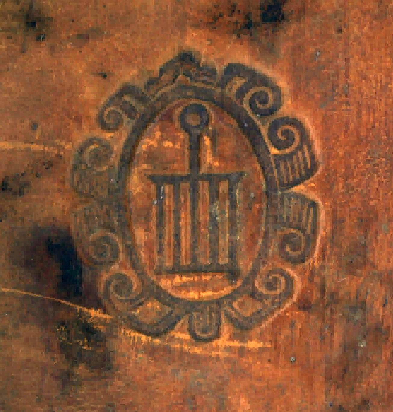 Supralibros de la Biblioteca de el Monasterio de El Escorial, gofrado, con la parrilla, emblema del monasterio, encuadrada en un marco ovalado