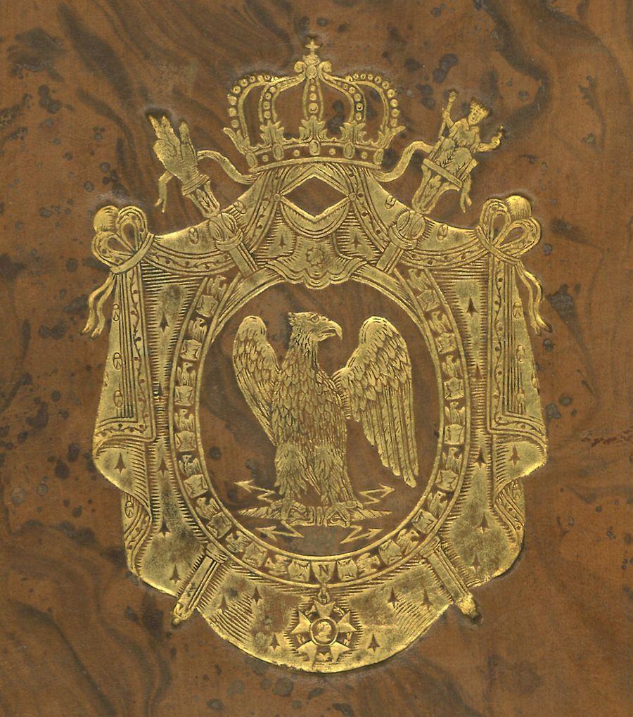 Supralibros heráldico con el escudo de armas de Napoleón I, Emperador de Francia, que representa un águila explayada y asiniestrada con un haz de rayos entre las garras, rodeado por el manto imperial decorado con abejas doradas,  coronado de corona imperial y en sotuer, bastones de cetro y mano de la justicia; collar de la Orden de la Legión de Honor